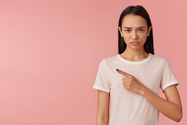 Портрет недовольной, сердитой девушки с длинными черными волосами. в белой футболке. смотрит и хмурится. указывая пальцем влево на место для копирования, изолированное на пастельно-розовой стене