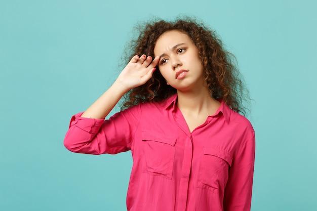 スタジオの青いターコイズブルーの壁の背景に孤立して脇を探しているピンクのカジュアルな服を着て不機嫌に泣いているアフリカの女の子の肖像画。人々の誠実な感情、ライフスタイルのコンセプト。コピースペースをモックアップします。
