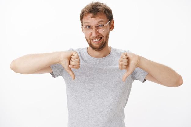 Портрет недовольного милого и забавного европейца в очках и серой футболке, показывающего большие пальцы вниз и гримасничающего от неприязни, выражающего неодобрение, будучи неудовлетворенным
