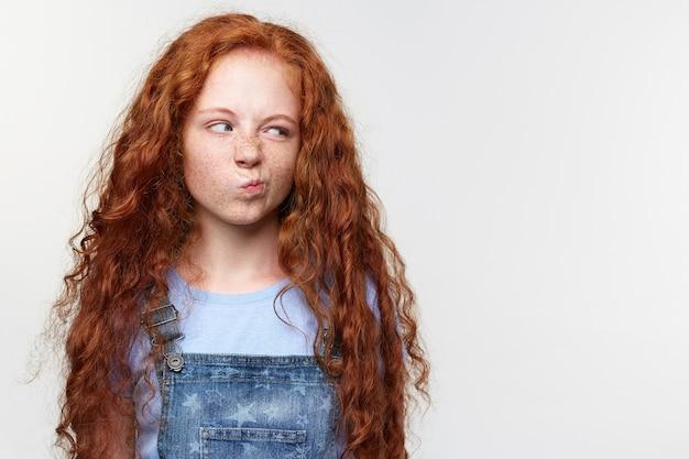 Портрет недовольной милой маленькой девочки с веснушками с рыжими волосами, с отвращением смотрит на место для копирования на левой стороне, танды на белом фоне.