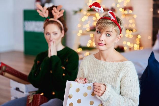 Портрет недовольной девушки, открывающей рождественский подарок