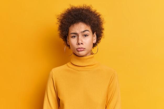 아프로 머리를 찡그린 얼굴을 가진 불쾌한 밀레 니얼 여성의 초상화는 불행한 느낌이 들며 캐주얼 터틀넥을 입은 몇 가지 문제가 있습니다.
