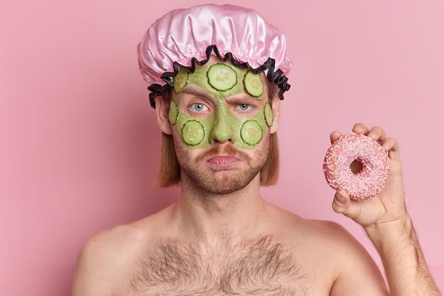 口ひげの眉をひそめている顔を持つ不機嫌な不機嫌そうな男の肖像画は、肌の若返りのために顔の緑のマスクキュウリのスライスを適用するトップレスの屋内でおいしいドーナツスタンドを保持しています。