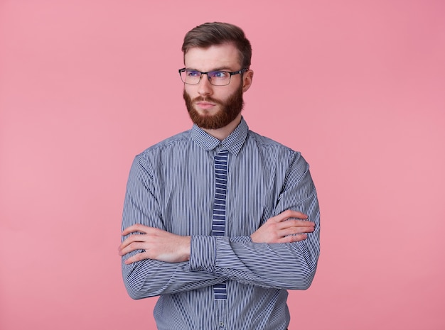 眼鏡とストライプのシャツを着た、不機嫌そうな若いハンサムな赤いひげを生やした男の肖像画は、ピンクの背景の上に立って、腕を組んで、目をそらします。
