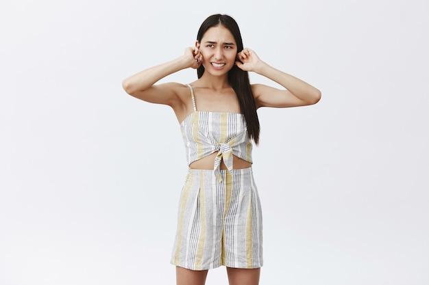 Портрет недовольной несчастной привлекательной молодой женщины в соответствующем топе и рубашке, закрывающей уши от дискомфорта, не желающей слышать тревожный громкий шум