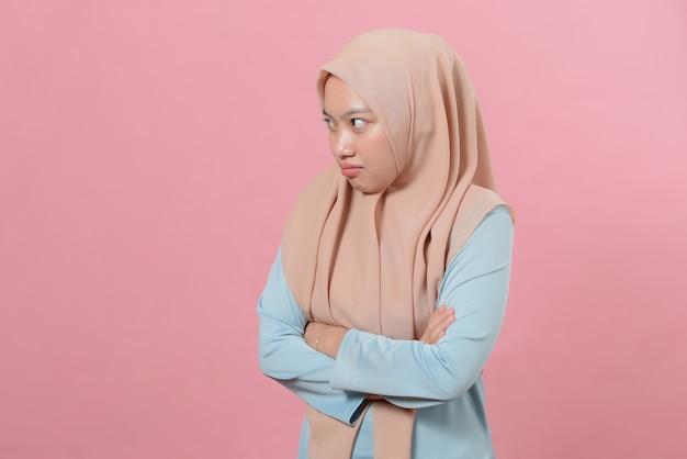 Портрет недовольной расстроенной мусульманской женщины хмурится, будучи недовольным и недовольным, поскольку не может достичь целей, изолированный на розовом фоне.