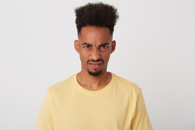 彼の顔を眉をひそめている暗い肌を持つ不機嫌な若い茶色の目のブルネットの男の肖像画