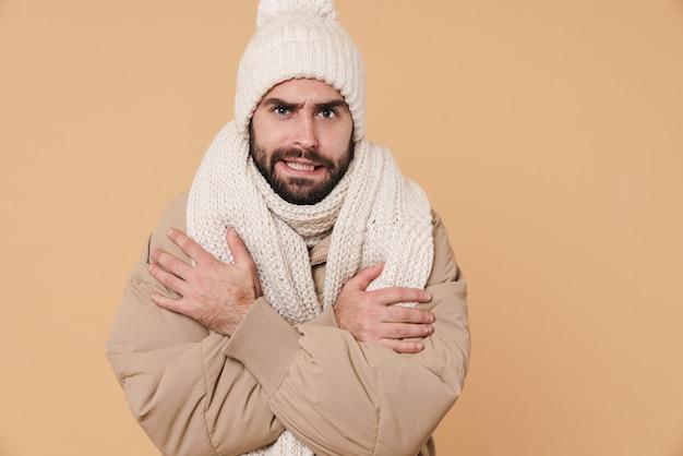 Портрет недовольного молодого человека в зимней одежде, дрожащего от холода, изолированного на бежевом