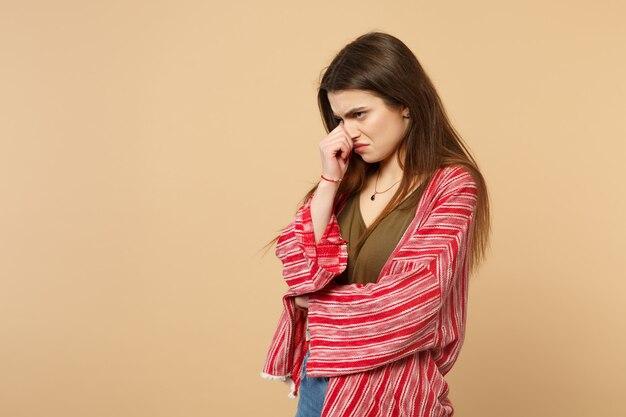 スタジオでパステルベージュの背景に分離された手で鼻を覆って脇を探しているカジュアルな服を着た不機嫌な若い女性の肖像画。人々の誠実な感情のライフスタイルの概念。コピースペースをモックアップします。