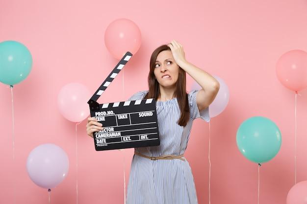 Портрет неудовлетворенной обеспокоенной женщины в синем платье, кусающей губы, цепляющейся за голову, держащей классическую черную пленку, делающую с 'хлопушкой' на розовом фоне с красочными воздушными шарами. праздник дня рождения.