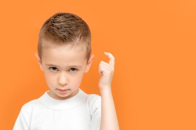 不満を持った少年の肖像画、指で頭をノックし、激しく残酷な表情を見せ、不満を持った眉をひそめます。
