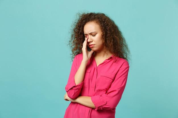 スタジオの青いターコイズブルーの壁の背景に分離された涙を拭き、泣いているカジュアルな服を着て不満の疲れたアフリカの女の子の肖像画。人々の誠実な感情、ライフスタイルのコンセプト。コピースペースをモックアップします。