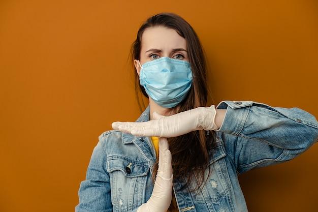 医療用滅菌フェイスマスク手袋の不満の女性の肖像画は、タイムアウトのジェスチャーを示し、停止する必要があり、茶色の壁の上に孤立しています。流行性パンデミック拡散コロナウイルス2019-ncov、インフルエンザウイルスのコンセプト
