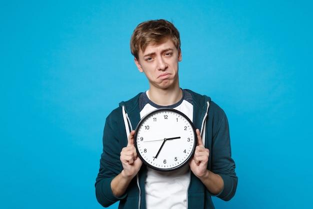 青い壁に隔離された丸時計を保持しているカジュアルな服を着た不満の若い男の肖像画。時間がなくなっています。人々の誠実な感情のライフスタイルの概念。