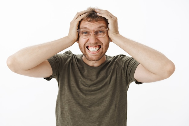 緑のtシャツとメガネで歯を食いしばって悩んで悩む若い男性会社員の肖像