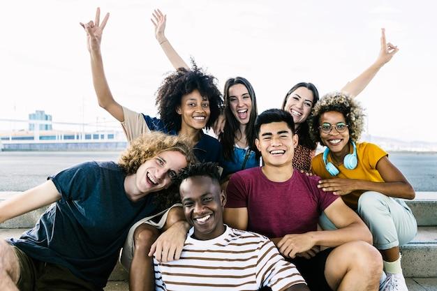Портрет разнообразных друзей колледжа, сидящих на городской лестнице