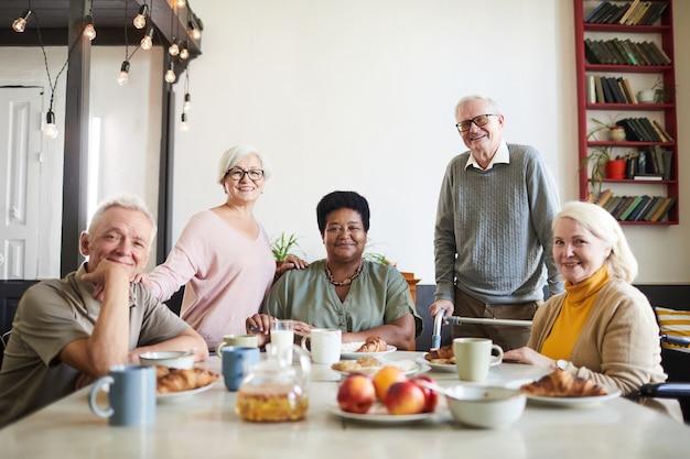 Портрет разнообразной группы улыбающихся пожилых людей, смотрящих в камеру в доме престарелых