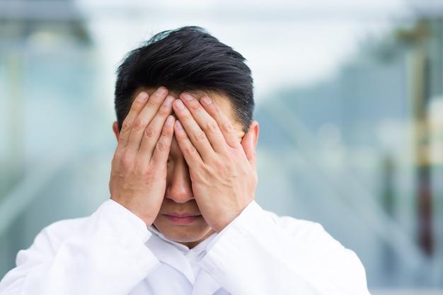 Портрет азиатского человека доктора устал после работы крупным планом фото