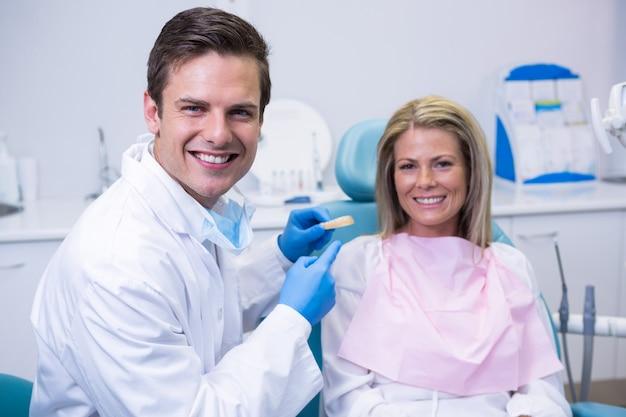 患者のそばに座っている間、歯科用金型を保持している医師の肖像画