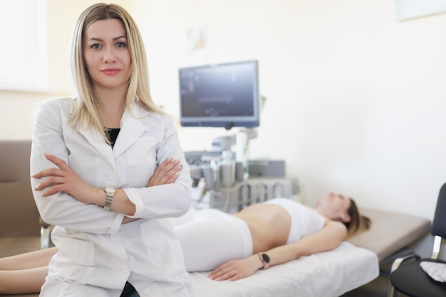 バックグラウンドで内臓の超音波検査のためのオフィスの医師の肖像画は患者です