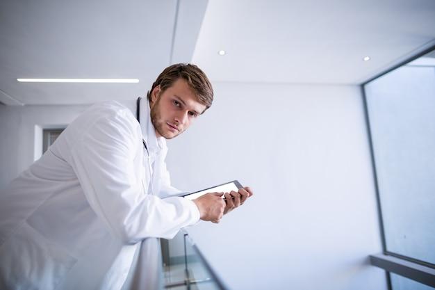 Портрет доктора, опираясь с цифровой планшет в коридоре