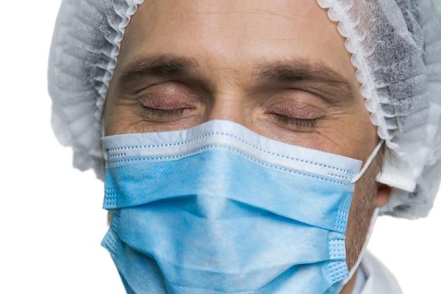 目を閉じて医師の顔の肖像画。白い壁に隔離された呼吸マスクの成熟した医師。