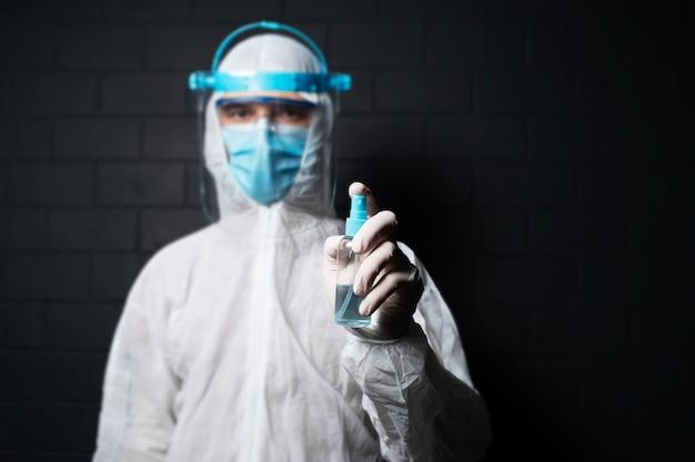 소독제 병 Spra를 들고 코로나 바이러스 및 Covid-19에 대한 Ppe 정장을 입고 의사의 초상화 프리미엄 사진