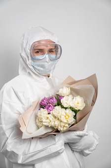 꽃의 꽃다발과 보호 복, 마스크, 안경 및 장갑에 의사 여자의 초상화.