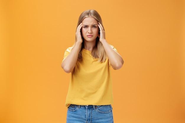 Портрет истощенной грустной молодой женщины и светлых волос, испытывающих дискомфорт в голове, касаясь висков, страдающих головной болью или мигренью, пытающихся сосредоточиться на работе