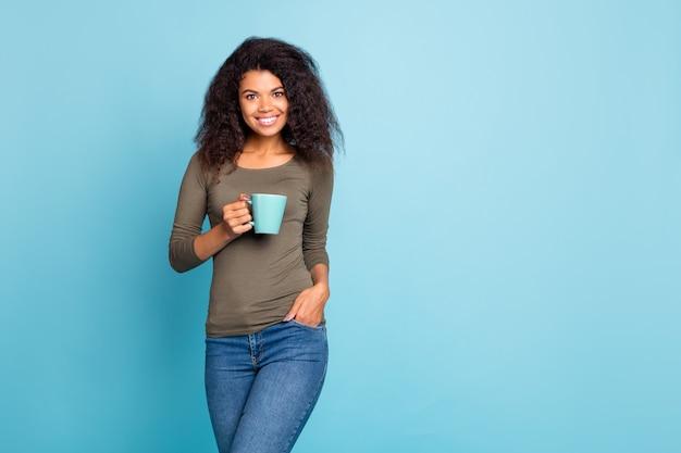 Портрет мечтательной позитивной жизнерадостной девушки-мулатки держит чашку с эспрессо какао чувствует себя довольной носить повседневную одежду джинсовые джинсы, изолированные на синей стене