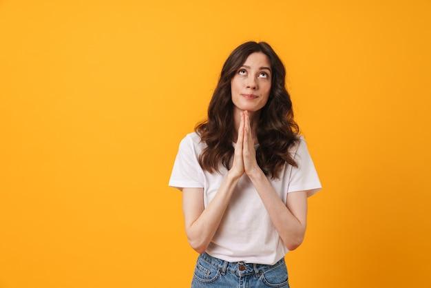 黄色い壁の上に孤立してポーズをとっている夢を見ている若い女性の肖像画は、脇を見てジェスチャーしてください。