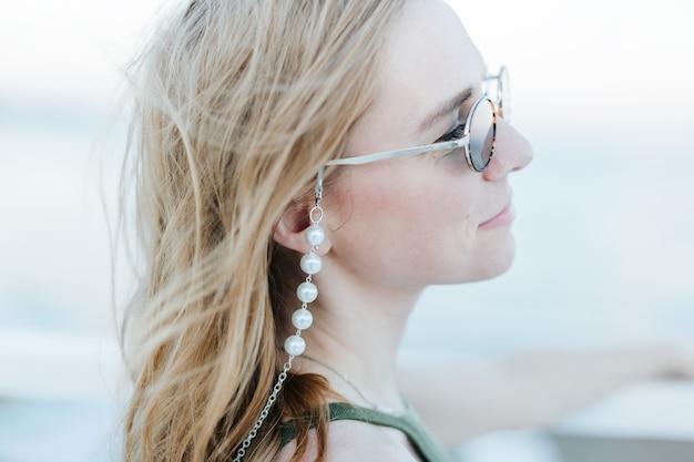 Портрет мечтательной кавказской смеясь над улыбающейся девушкой-женщиной в солнечных очках на открытом воздухе на фоне пляжа.
