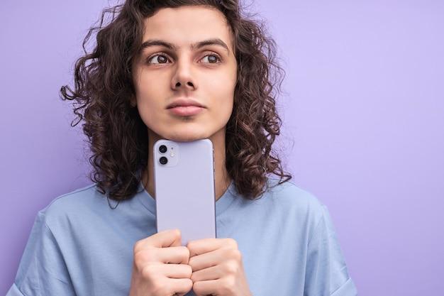 Портрет мечтательного кудрявого парня, держащего смартфон в руках, смотрящего в сторону, наслаждающегося общением с друзьями, изолированного на фиолетовом фоне