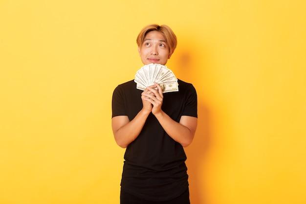 Портрет мечтательного красивого азиатского парня, показывающего свои сбережения и размышления, смотрящего в левый верхний угол, держащего деньги, стоящего у желтой стены