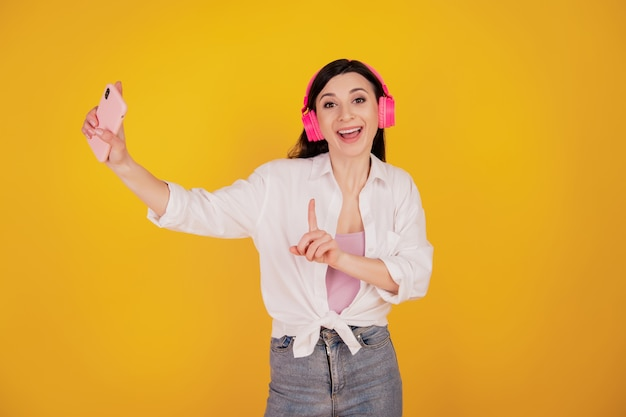 Портрет мечтательной вдохновленной девушки держит мобильный телефон в наушниках танцует на желтом фоне