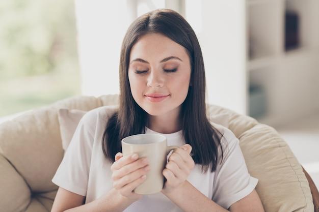 夢のようなかわいい女の子の肖像画は、屋内の家で椅子の香りの芳香のコーヒーカップに座る