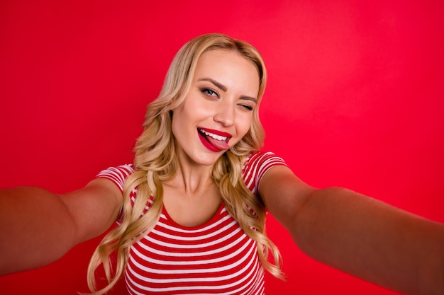Портрет мечтательной романтической девушки делает селфи, показывая язык, моргая
