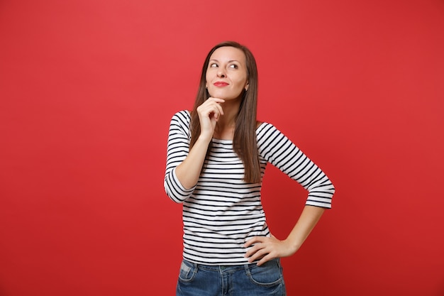 Портрет мечтательно улыбающейся молодой женщины в полосатой одежде смотрит вверх, подпирая подбородок рукой