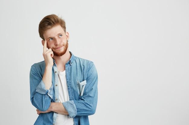 Портрет мечтательного молодого человека думая смотреть вверх с рукой на щеке.