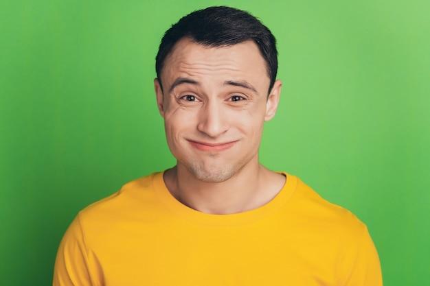 녹색 배경에 우둔한 얼굴을 어깨를 으쓱하는 벙어리 불확실한 남자의 초상화