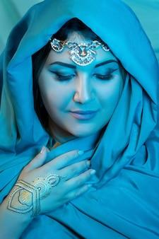 青いスカーフと東部の女性のクローズアップの肖像画。アラビアの女性。