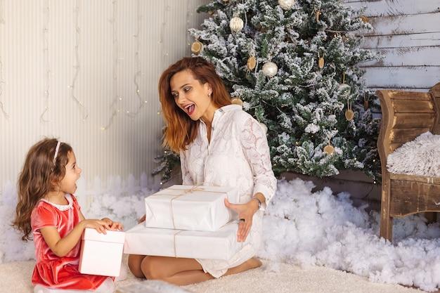 Портрет возбужденной матери и дочери с подарочными коробками