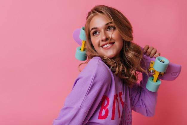 夢のような見上げるロングボードを持つ恍惚とした白人の女の子の肖像画。ピンクのスケートボードと壮大な金髪の女性モデルの肖像画。