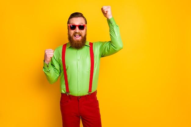 恍惚とした陽気なひげを生やした幸運な男の肖像は拳を上げる宝くじの悲鳴を勝ち取るええ、輝きの色の上に分離された格好良い服のズボンを着用してください