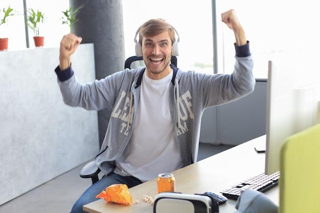 コンピューターでビデオゲームをプレイしながら叫び、歓喜するヘッドフォンで恍惚としたゲーマーの男の肖像画。