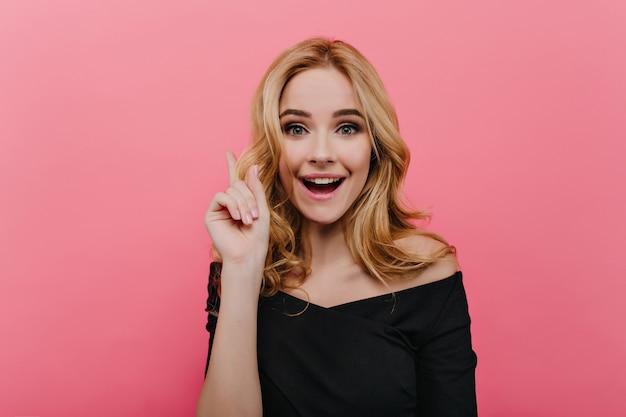 밝은 분홍색 벽에 웃고 행복한 얼굴 표정으로 황홀한 젊은 여자의 초상화. 사랑스러운 여성 모델의 실내 사진은 우아한 검은 옷을 입고 있습니다.