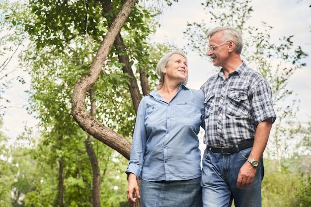 緑の木々を背景に笑顔と抱擁を愛する老夫婦の肖像画