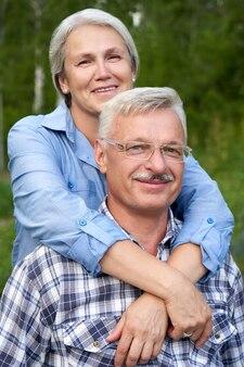 웃 고 푸른 나무의 배경에 대해 포옹 사랑에 노인 부부의 초상화