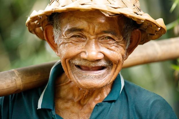 彼の田んぼに取り組んでいるバリ島の高齢のイドネシアの農民の肖像画