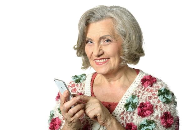 Портрет пожилой женщины с мобильным телефоном и фотографией на белом фоне